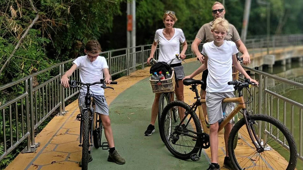 Family on bamboo bikes in Bangkok.