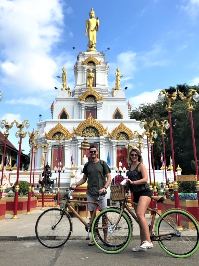 Cyclists in front of a Buddhist temple Bangkok