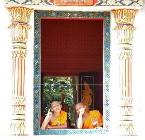 Two friendly monks waiving from a temple